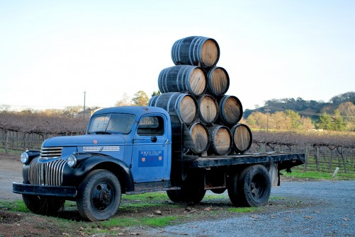 A pyramid of 10 oak wine barrels on the bed of an antique truck