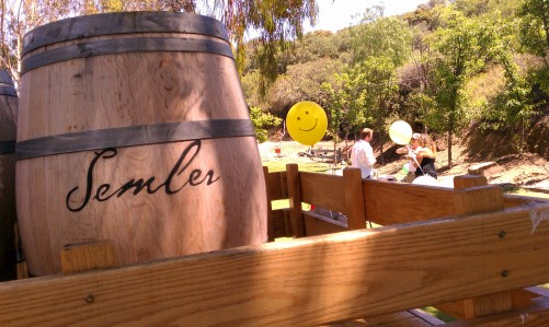 Smiley-face balloon next to a wine barrel